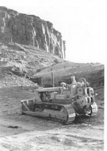 Theodore learning to operate a cat, in the evening, July, 1955.  The cliff is Wingate Sandstone and it is named Copper Point because of the late 19th Century Four Aces copper mine just below it.  The soft formation sloping up from the cat parking place to the Wingate is Chinle shale.  It is the shale of the Painted Desert and the Petrified Forest National Parks.   Note the cat built, switch back road up to the base of the Wingate.
