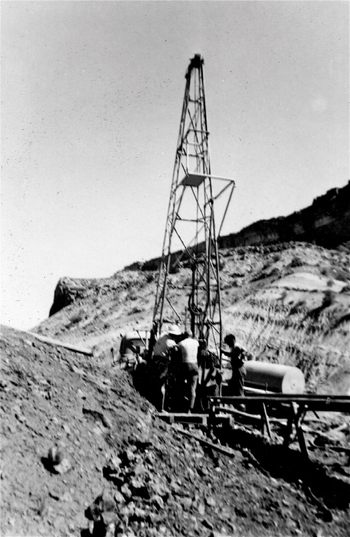 A drilling rig at Four Aces Claim in August 1955 with the sloping Chinle shale mostly hiding the tall Wingate cliffs of Copper Point. (Most crews had one driller often in his 20s and two teenage kids. The latter often liked to shoot at the common, tiny (6 to 10 inches long and under 1/2 inch diameter) sidewinders. Since we all wore boots this shooting was much more dangerous (bullets fly off rocks in surprising directions) than the snakes themselves. They are only dangerous when you sleep on the ground. They may slide into your sleeping bag to escape the cold desert nights and if you role over a bite in the wrong place could easily be fatal.